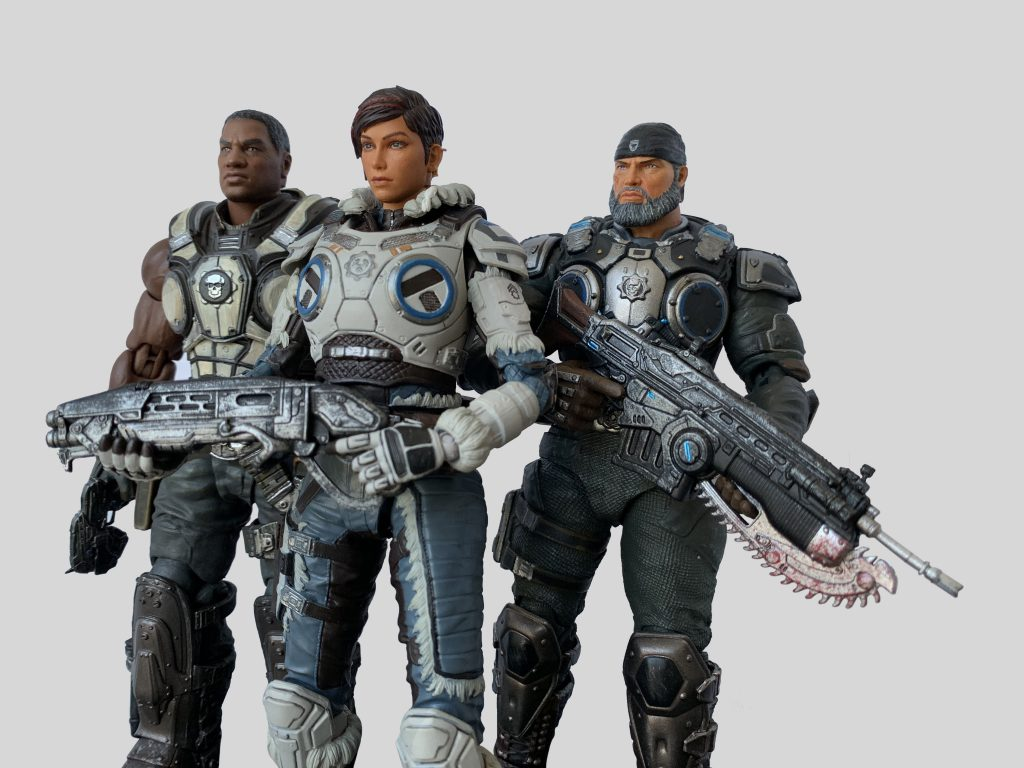 Augustus Cole and Marcus Fenix figures standing at the ready, with Kait Diaz leading the squad.