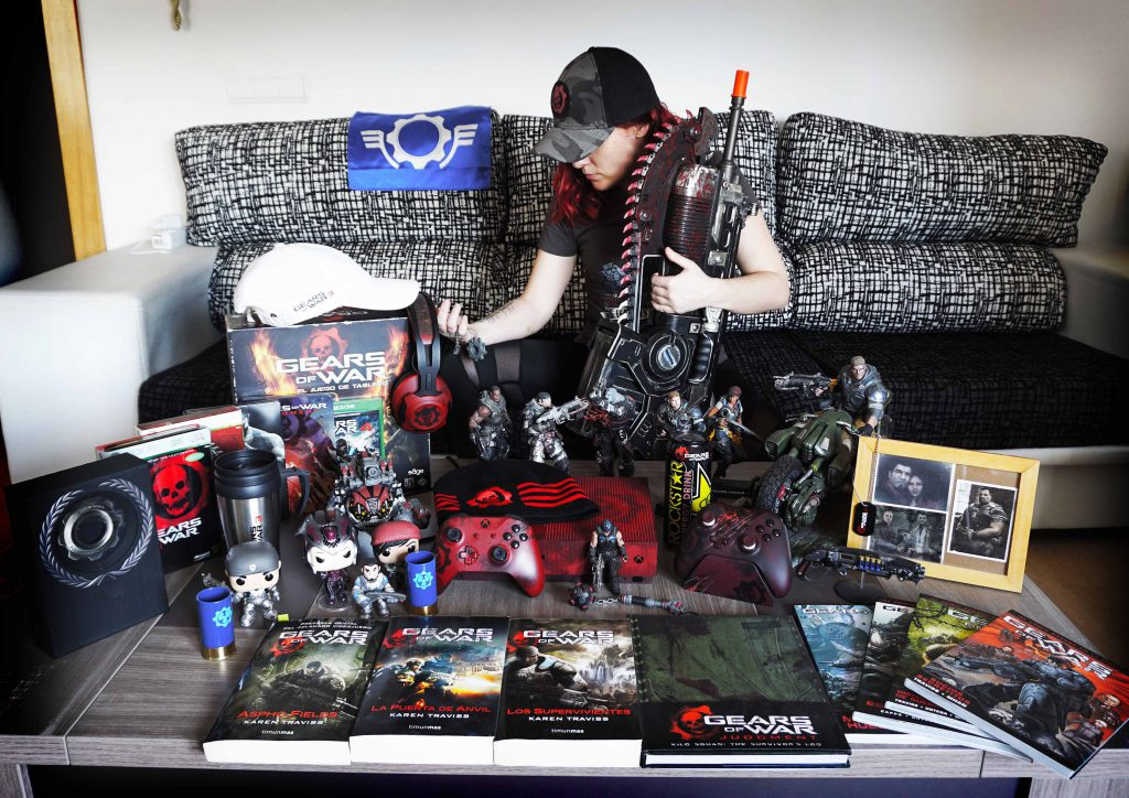 """Twitter user """"LadyBoss"""" sitting on a sofa and showing off their collection of Gears-related collectibles"""